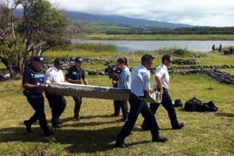 Anggota kepolisian Pulau Reunion membawa potongan logam yang diduga adalah bagian sayap pesawat Boeing milik Malaysia Airlines MH370 yang hilang lebih dari satu tahun yang lalu.