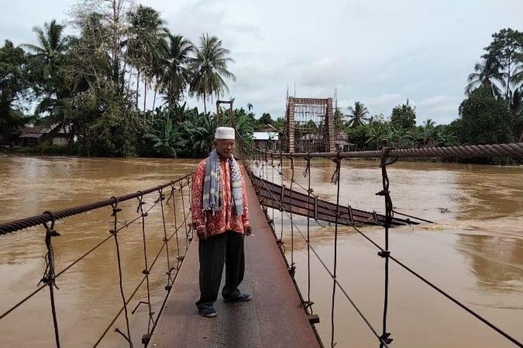 Warga Desa Karang Birahi, Haji Zainul saat memperlihatkan jembatan gantung yang putus akibat diterjang banjir