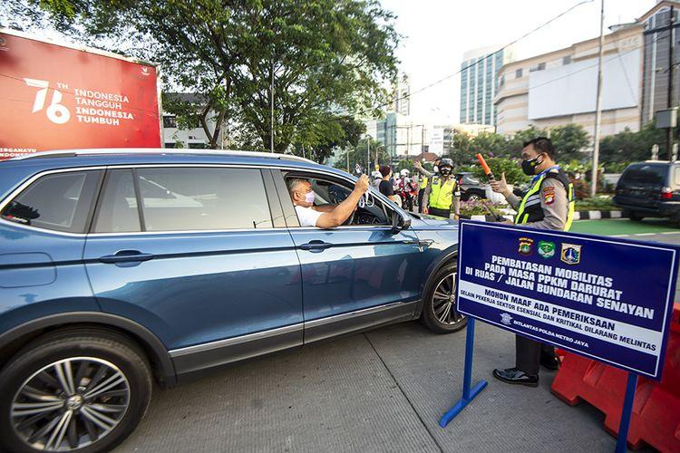 Anggota Polisi mengacungkan jempol pada pengendara mobil yang menunjukkan surat undangan vaksin COVID-19 di Gelora Bung Karno, Senayan saat berlangsungnya Pemberlakuan Pembatasan Kegiatan Masyarakat (PPKM) Darurat di kawasan Bundaran Senayan, Jakarta, Sabtu (3/7/2021). Petugas akan memberikan akses untuk melintas di titik penyekatan PPKM Darurat di 63 titik di wilayah Jadetabek yang berlaku dari 3 - 20 Juli 2021 hanya yang masuk kategori sektor-sektor esensial. ANTARA FOTO/M Risyal Hidayat/hp.