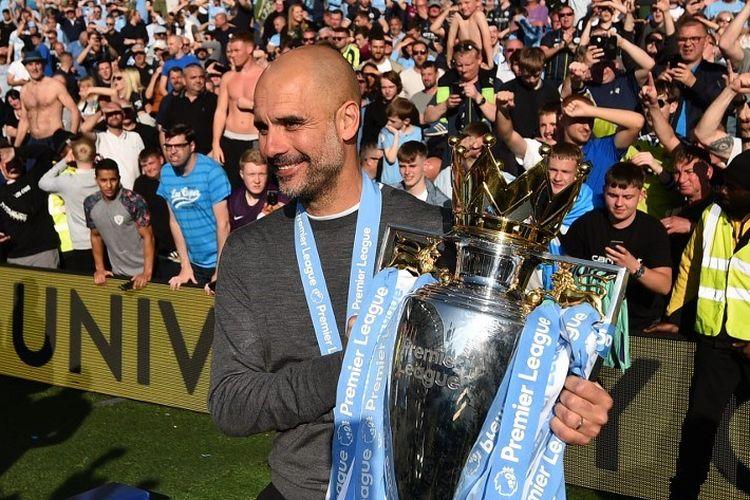 Pep Guardiola mengangkat trofi Premier League seusai Manchester City memastikan diri menjadi juara Liga Inggris pada laga versus Brighton & Hove Albion di Stadion American Express Community, 12 Mei 2019.