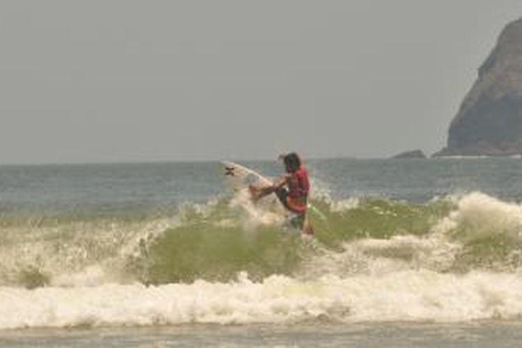 Salah satu peselancar usia anak anak sedang bermain di Pantai Pulau Merah Banyuwangi pada Kompetisi Surfing Internasional yang digelar pada 25-27 September 2015