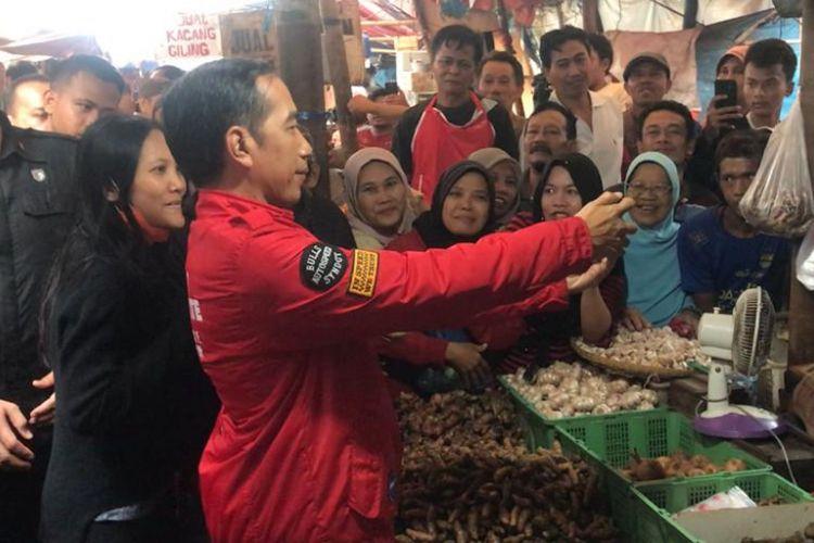 Presiden Joko Widodo saat berselfie bersama warga di Pasar Anyar, Kota Tangerang, Banten, Minggu (11/4/2018).