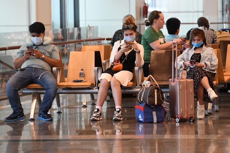 Penumpang mengenakan masker untuk melindungi diri dari penyebaran Covid-19 coronavirus, saat menunggu penerbangan di Bandara Internasional Changi, di Singapura, 27 Februari 2020