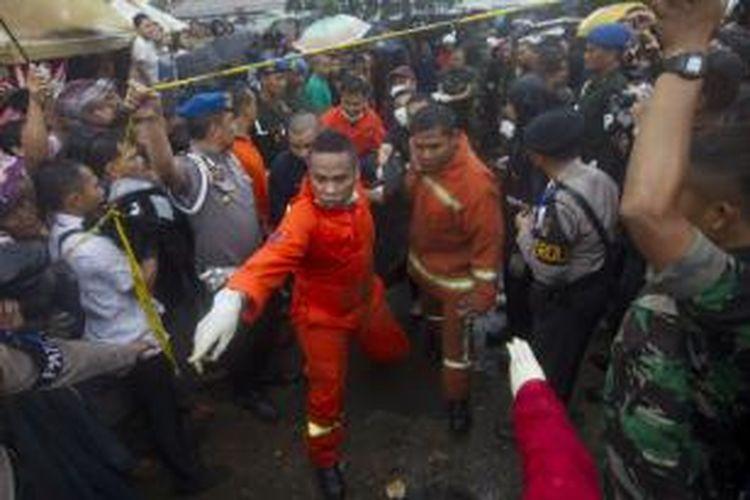 Petugas berusaha mengevakuasi korban di lokasi tabrakan kereta rel listrik (KRL) jurusan Serpong-Tanah Abang dengan truk tangki pengangkut bahan bakar di pelintasan Pondok Betung, Bintaro, Jakarta Selatan, Senin (9/12/2013). Kecelakaan mengakibatkan sejumlah rangkaian gerbong dan truk tangki terbakar, menyebabkan 10 orang tewas dan puluhan orang luka-luka.