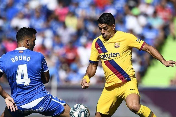 Penyerang Barcelona Luis Suarez (kanan) berusaha melewati hadangan bek Getafe Bruno dalam pertandingan Liga Spanyol di Stadion Col. Alfonso Perez, Sabtu (28/9/2019).