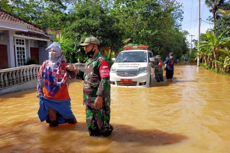 Para anggota TNI Koramil Pagerageung Kodim 0612 Tasikmalaya membantu tenaga medis dan mobil ambulans membawa vaksin Covid-19 di lokasi banjir musiman Jalan Karangresik, Kabupaten Tasikmalaya, Kamis (25/3/2021).