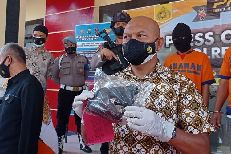 Kasat Reskrim Polres Magetan (tengah), memperlihatkan air softgun yang mirip dengan senjata apai pistol yang digunakan tersangka SN untuk menganiaya TP 18. Polisi masih melakukan pendalaman terkait kepemilikan air softgun tersebut.