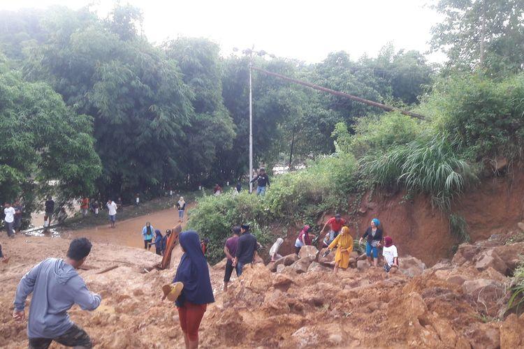 Warga Desa Rumbia, Kabupaten Jeneponto, Sulawesi Selatan berusaha menorobos longsoran yang mengakibatkan tiga warga hilang. Sabtu, (13/6/2020).