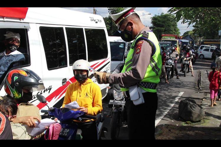 Petugas kepolisian melakukan pengecekan dukumen perjalanan di Mengwi, Badung, Bali