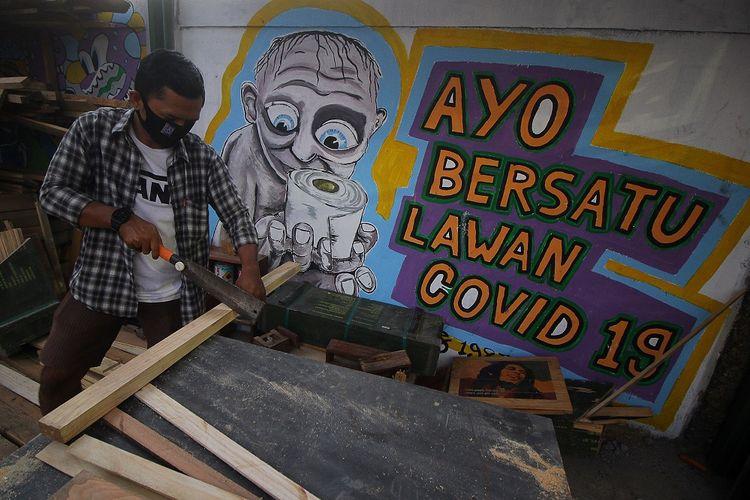 Warga beraktivitas di depan mural tentang COVID-19 di Kampung Jogoloyo, Surabaya, Jawa Timur, Senin (27/7/2020). Berdasarkan data dari Satgas Penanganan COVID-19 per 27 Juli 2020, kasus positif COVID-19 di Indonesia telah mencapai 100.303 kasus, dimana 58.173 orang dinyatakan sembuh dan 4.838 orang meninggal dunia. ANTARA FOTO/Moch Asim/pras.