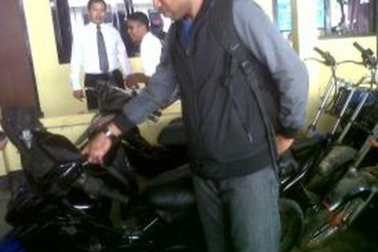 Seorang petugas kepolisian menunjukkan motor hasil curian tiga pelajar di Ambon.