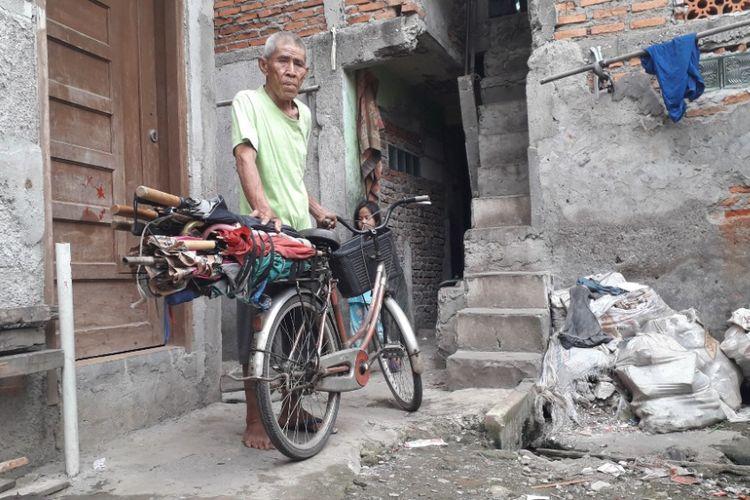 Kong Muin berpose di depan sepedanya yang ia gunakan dalam menjajakan keahliannya sebagai tukang servis payung, Jumat (1/2/2019).
