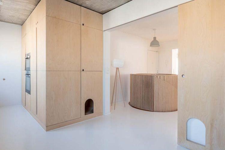 Material sederhana berupa beton, resin putih, dan birch plywood yang mendominasi hunian
