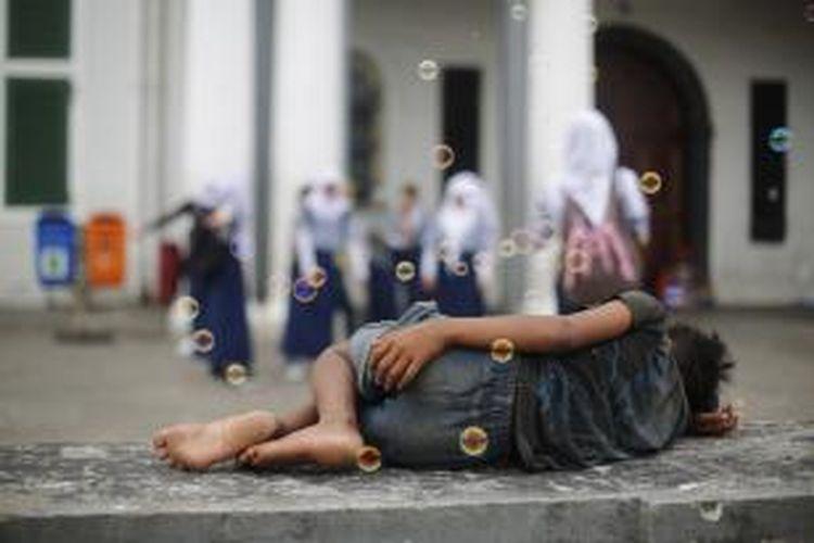 Anak jalanan terlelap di kawasan Kota Tua di Taman Fatahillah, Jakarta Barat, Sabtu (8/3). Keberadaan rumah singgah harusnya diperbanyak untuk alternatif memberdayakan anak-anak yang secara bentukan mental emosional belum kokoh ini. Kompas/Agus Susanto (AGS)