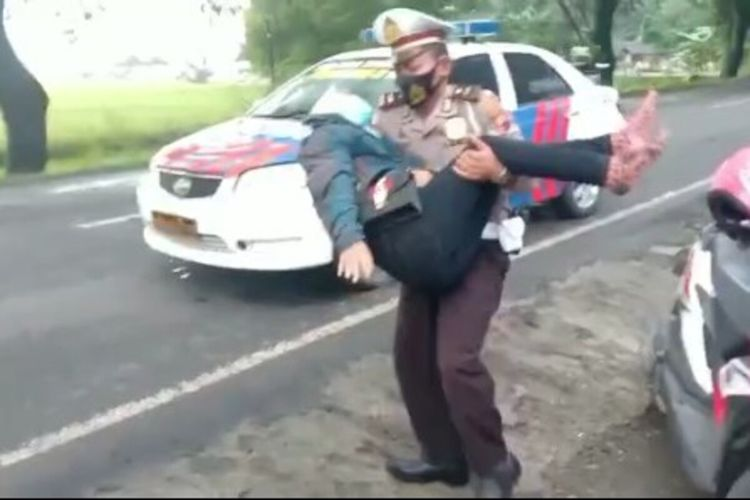 Kanit Dikyasa Satlantas Polres Sragen Ipda Sigit Krisyanto (40) saat membopong pengendara motor yang terjatuh di jalan berlubang di Sragen, Jawa Tengah pada Sabtu (13/2/2021).