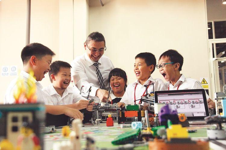 Siswa-siswi Sinarmas World Academy sedang mempelajari robotik di ruang kelas.