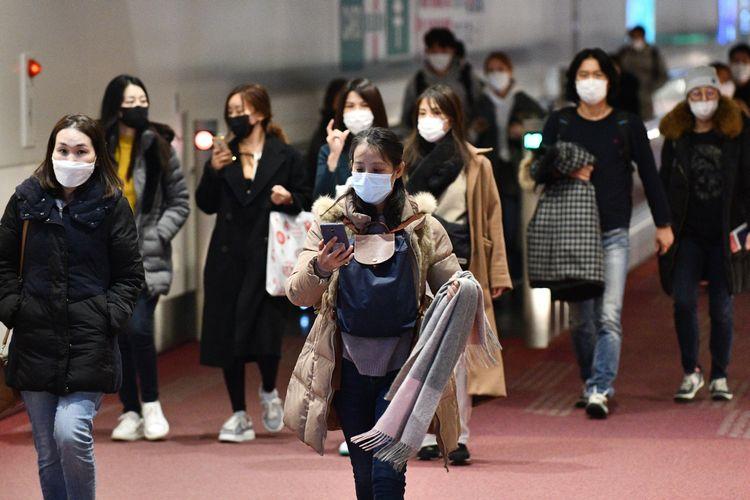 Penumpang dari luar negeri menggunakan masker untuk mencegah penyebaran virus Corona saat tiba di Bandara Internasional Haneda, 28 Januari 2020.