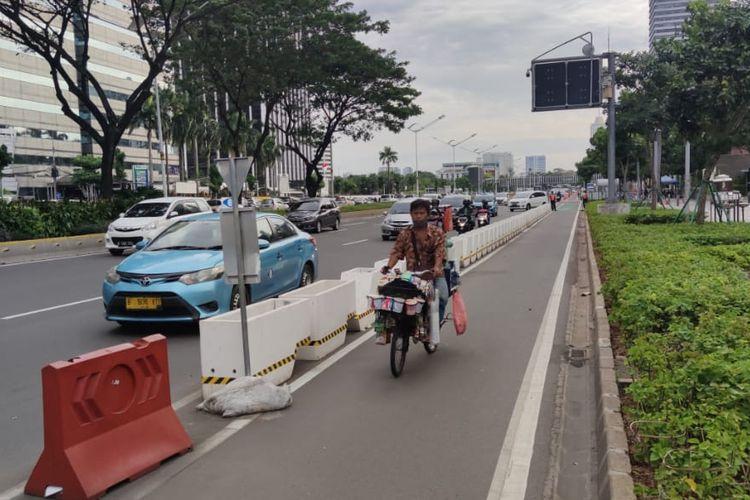 Pedagang kopi keliling, Jaelani (41) melintasi jalur sepeda permanen di Jalan Sudirman, Jakarta, Kamis (17/6/2021).