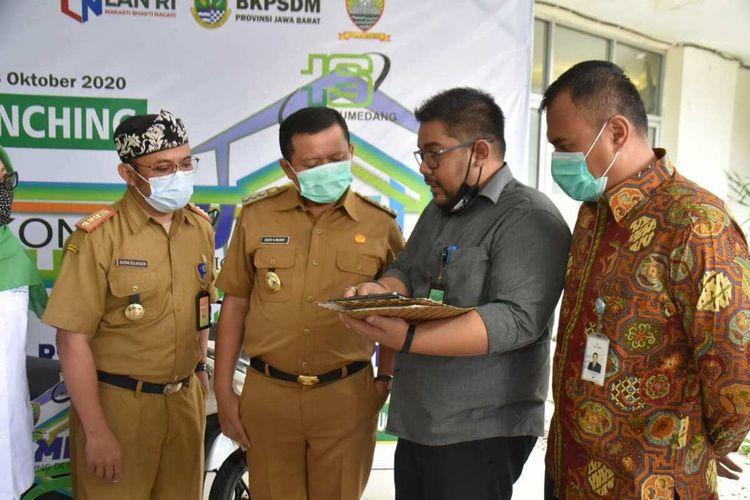 Humas RSUD Sumedang menunjukkan cara mengakses aplikasi Koncibumi kepada Bupati Sumedang H Dony Ahmad Munir, Senin (26/10/2020). AAM AMINULLAH/KOMPAS.com