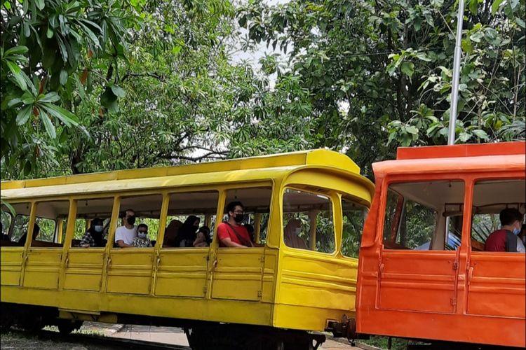 Pengunjung Taman Mini Indonesia Indah (TMII), Jakarta Timur, memanfaatkan fasilitas kereta. Foto diambil pada Sabtu (27/3/2021).