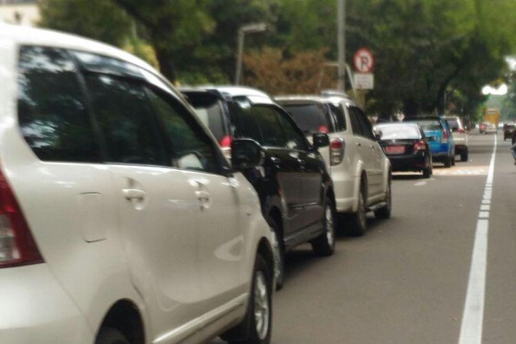 Lajur paling kiri yang diperuntukkan bagi pengendara sepeda motor dijadikan tempat parkir mobil di Jalan Medan Merdeka Barat, Rabu (24/1/2018).