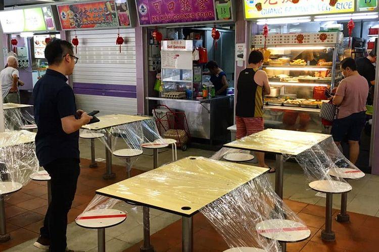 Terlihat meja-meja di Pasar dan Pusat Makanan Blok 112 Bukit Merah, Singapura Tengah disegel dengan plastik, Kamis pagi (09/04/2020). Sesuai arahan kebijakan circuit breaker atau separuh lockdown, makanan yang dibeli warga Singapura dilarang dikonsumsi di tempat dan harus disantap pulang di kediaman masing-masing.