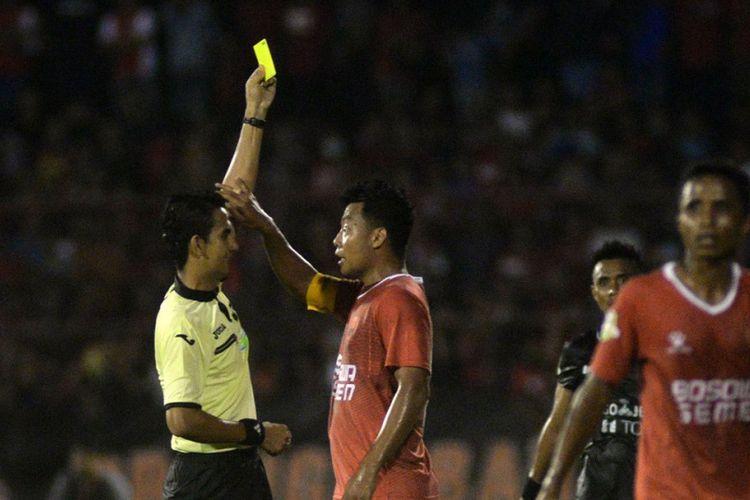 Kapten PSM Makassar, Hamka Hamzah, berbincang dengan wasit dalam laga Liga 1 kontra Persija Jakarta di Stadion Andi Mattalatta, Minggu (30/4/2017).