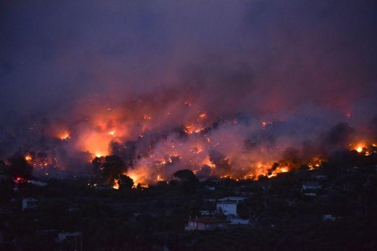 Kebakaran hutan di kota Rafina, dekat Athena, Yunani, pada Senin (23/7/2018). (AFP/Angelos Tzortzinis)