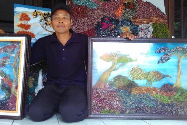 Muhdi memperlihatkan lukisan kain perca batik hasil karyanya.