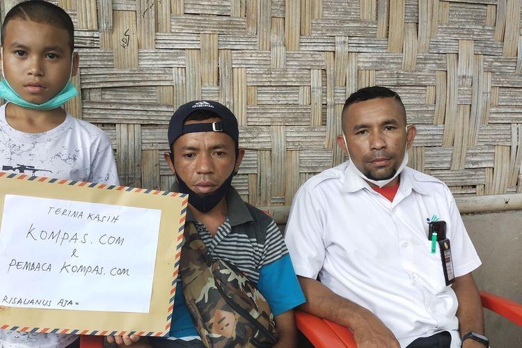 Dari Kiri ke kanan-Risalianus Aja sedang memegang kertas bertuliskan Terima Kasih KOMPAS.com dan Pembaca KOMPAS.com didampingi pamannya, Juvensius Lavi serta penghubung selama ini Maksimus Ekung di kampung Peot, Kelurauan Peot, Rabu,.(15/9/2021). (KOMPAS.com/MARKUS MAKUR)
