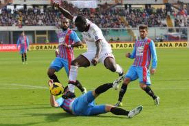 Striker AC Milan, Mario Balotelli saat berusaha merebut bola dari pemain Catania pada lanjutan Serie-A di Stadion Angelo Massimino, Minggu (1/12/2013). Milan menang 3-1 pada pertandingan tersebut.