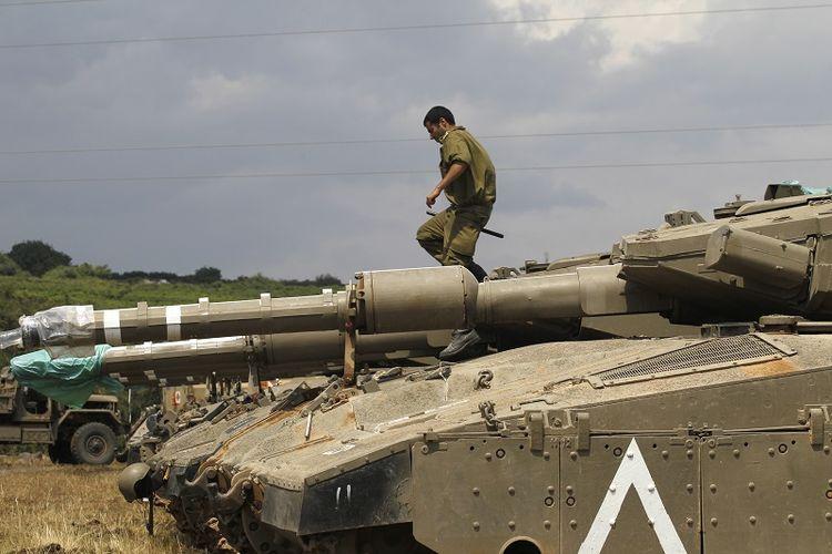 Seorang prajurit Israel tengah berdiri di atas tank Merkava IV yang disiagakan di Dataran Tinggi Golan yang berbatasan dengan Suriah.