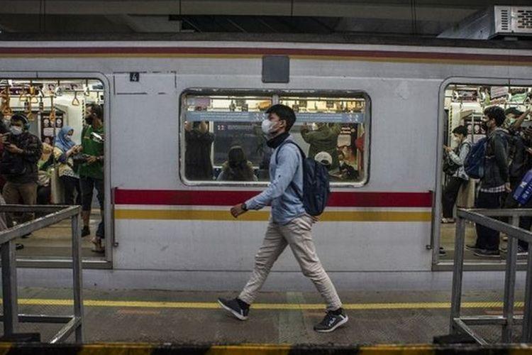 Seorang warga yang mengenakan masker melenggang di depan rangkaian kereta rel listrik (KRL) di Stasiun Manggarai, Jakarta, Kamis (06/05).
