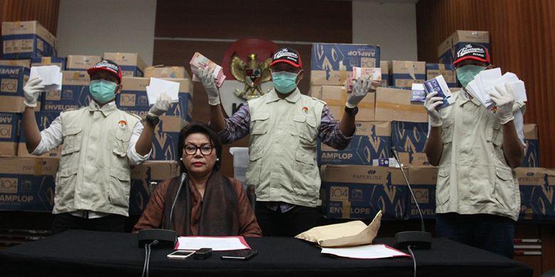 Penyidik didampingi Wakil Ketua KPK Basaria Panjaitan, menunjukkan barang bukti hasil operasi tangkap tangan (OTT) yang menjerat anggota DPR Fraksi Golkar Bowo Sidik Pangarso, saat memberikan keterangan pers, di Gedung KPK Merah Putih, Jakarta, Kamis (28/3/2019). Uang senilai Rp 8 miliar yang dibagi dalam 84 kardus atau 400 ribu amplop dengan pecahan Rp 20 ribu dan Rp 50 ribu tersebut diduga sebagai suap untuk pelaksanaan kerja sama Pengangkutan Bidang Pelayaran antara PT Pupuk Indonesia Logistik (PILOG) dan PT Humpuss Transportasi Kimia (HTK), dan diduga digunakan untuk membantu biaya kampanye 2019.