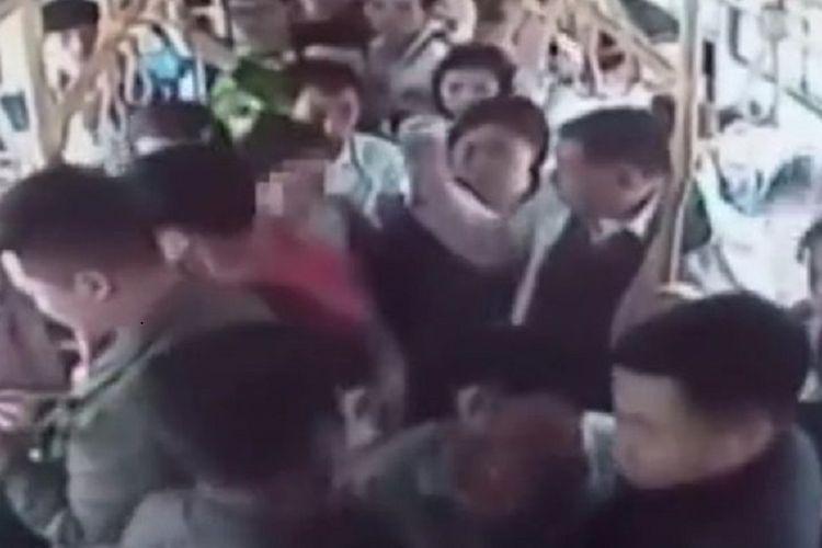 Foto yang diambil dari rekaman CCTV ini memperlihatkan penumpang sebuah bus di kota Yibin, China menangkap pelaku pelecehan seksual (wajah diburamkan) dan menyerahkannya ke polisi.