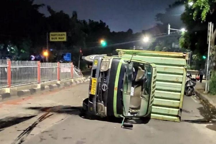 Truk boks bermuatan sembako terguling di Jalan Raya Pondok Gede, Kramat Jati, Jakarta Timur, Minggu (5/4/2020). Petugas evakuasi menyebutkan truk berbobot 13 ton itu mengangkut sembako untuk dipasok menuju minimarket di Jakarta.