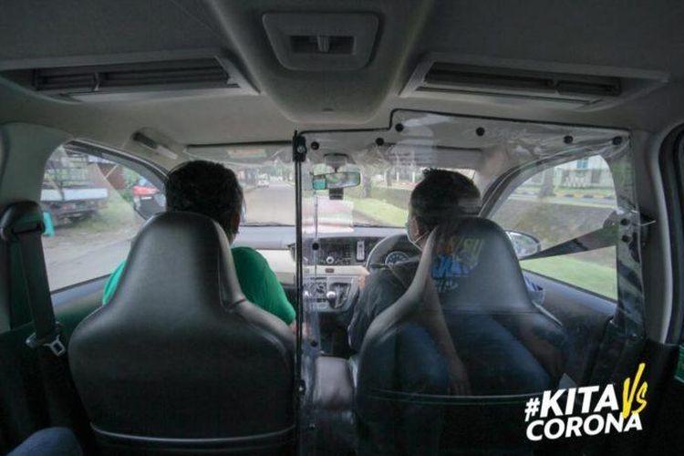 Mitra Pengemudi GrabCar dan penumpang dipisahkan dengan partisi plastik agar baik Mitra Pengemudi dan penumpang saling menjaga satu sama lain.