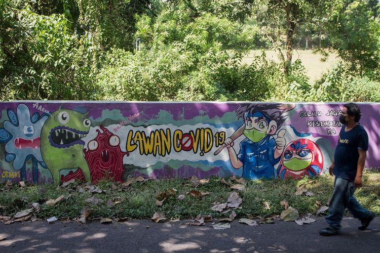 Pengendara melintas di depan mural bertema Lawan COVID-19 di Kampung Gulon, Jebres, Solo, Jawa Tengah, Rabu (16/6/2021). ANTARA FOTO/Mohammad Ayudha/foc.