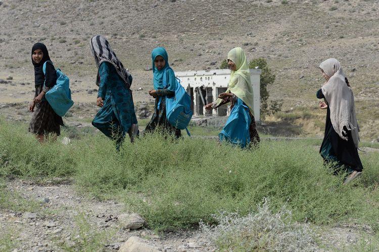 Foto yang dirilis pada 22 Juli 2019 memperlihatkan anak-anak sekolah di Afghanistan tengah pulang sekolah di SMP Papen yang hancur di distrik Deh Bala, Provinsi Nangarhar.