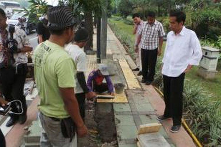 Gubernur DKI Jakarta Joko Widodo (kanan) meninjau perbaikan trotoar Jalan Gatot Subroto, Jakarta Selatan, Sabtu (28/9/2013).