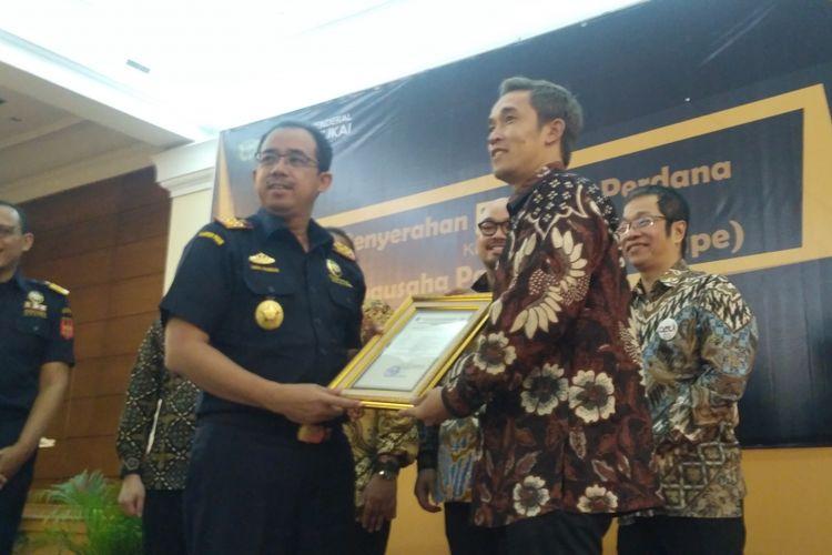 Direktur Jenderal Bea dan Cukai Heru Pambudi menyerahkan Nomor Pokok Pengusaha Barang Kena Cukai (NPPBKC) kepada sejumlah pengusaha liquid vape di Aula Merauke kantor Direktorat Jenderal Bea dan Cukai, Jakarta, Rabu (18/7/2018).