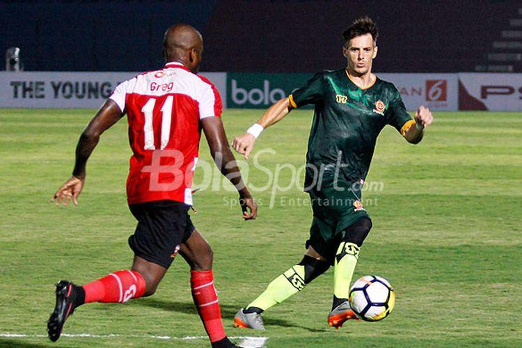Aksi pemain sayap PS Tira, Mariano Berriex (kanan), berhadapan dengan striker Madura United, Greg Nwokolo, dalam laga lanjutan Liga 1 2018 di Stadion Sultan Agung Bantul, Senin (2/4/2018).