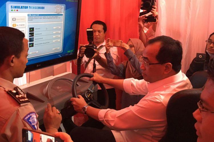 Menteri Perhubungan Budi Karya Sumadi mencoa simulator mengemudi di acara Pembuatan SIM A Umum di Stadion Gelora Bung Karno, Minggu (25/2/2018)