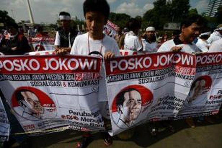 Puluhan orang yang tergabung dalam Barisan Relawan Jokowi membentangkan spanduk dukungan untuk calon presiden dari PDI-P Joko Widodo di depan Istana Negara, Jakarta, Minggu (4/5/2014).