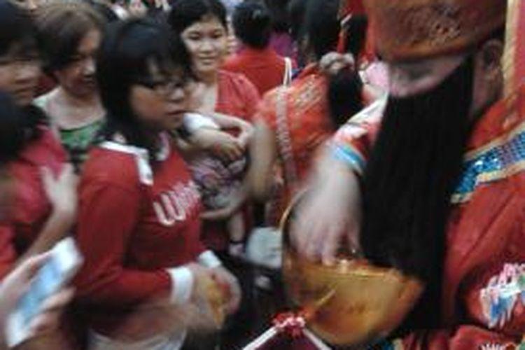 Tampak salah satu kegiatan bagi-bagi angpao oleh salah satu anggota wihara dengan kostum Cai Shen sang Dewa Kekayaan.