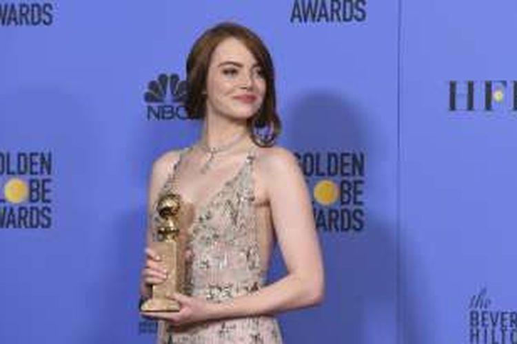 Aktris Emma Stone berpose bersama trofi aktris terbaik untuk film musikal/komedi pada ajang Golden Globe Awards 2017 yang digelar di Beverly Hills, California, Minggu (8/1/2017).