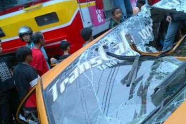 Taksi berwarna kuning ditabrak KRL Commuter Line di pintu perlintasan Cipinang, Jakarta Timur, Rabu(6/11/2013).