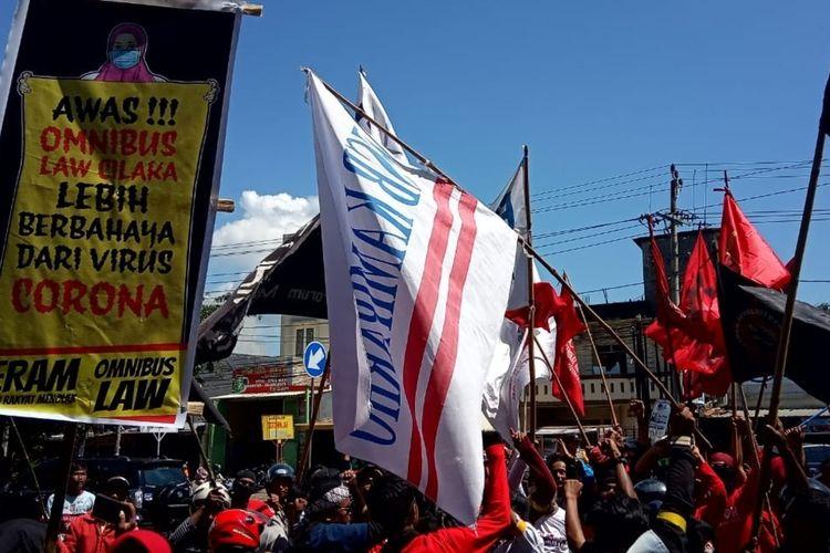Para buruh di Makassar saat menggelar aksi penolakan omnibus law Rancangan Undang-undang Cipta Kerja di depan kantor Gubernur Sulawesi Selatan, Jalan Perintis Kemerdekaan, Makassar, Rabu (11/3/2020).