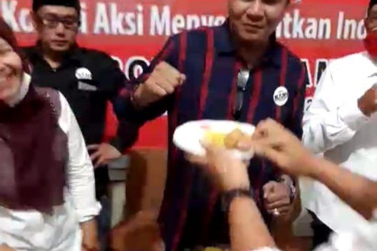 Presidium KAMI Jambi Amrizal Ali Munir memotong tumpeng setelah bernegosiasi dengan pihak kepolisian yang membubarkan acara deklarasi, Jumat (30/10/2020).