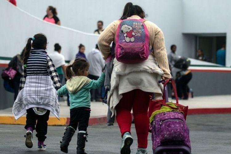 Migran berjalan menuju pelabuhan El Chaparral di Tijuana, Meksiko, di perbatasan dengan AS.